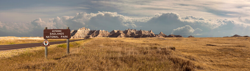 Wide landscape panoramic of badlands national park with signage entering into storm clouds