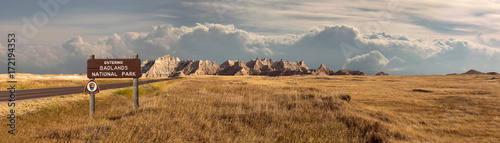 Wall Murals Natural Park Wide landscape panoramic of badlands national park with signage entering into storm clouds