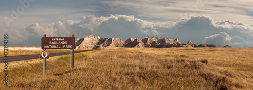 Wall Murals Natural Park Landscape panorama of badlands Rocky Mountain range, clouds, and grassland with sign