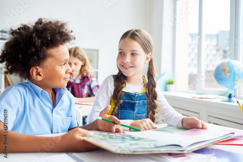 Friendly classmates with open book of tales having discussion on background of schoolboy