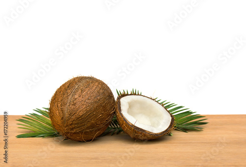 Fotografía  Coconut (Cocos nucifera) with half and palm leaves on wooden table on a white ba