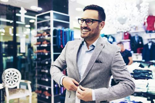 Plakat Uśmiechnięty młody człowiek, kupując ubrania