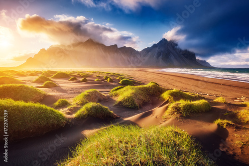 Beautiful view of the yellow hills glowing by sunlight. Location place Stokksnes cape, Vestrahorn, Iceland, Europe.