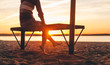 Woman sitting on beach bench swinging legs