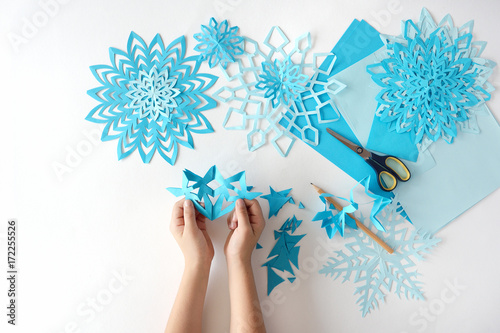 Foto  Making of snowflakes from blue paper.