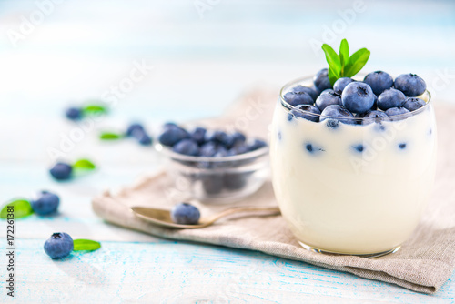 clear-jar-of-yogurt-with-blueberries-over-on-wooden-background
