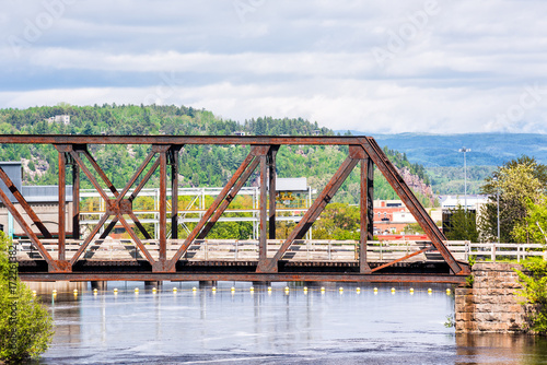 Fototapeten Forest river Cityscape or skyline of city of Saguenay, Canada in Quebec with Chicoutimi river and water flowing in summer with rusty bridge covered in rust