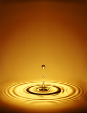 Droplet With Ripples In Amber Liquid