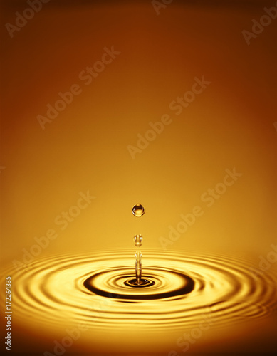 Fototapeten Natur Droplet with ripples in amber liquid
