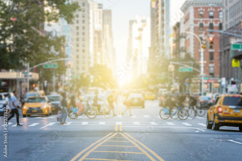 People crossing the busy intersection between traffic on 3rd Avenue and 10th Street in Manhattan in New York City with the glow of sun light in the background