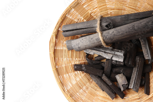 Charcoal in basket on white background. Free space for text Wallpaper Mural