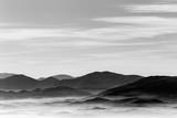 Widok z góry na dolinę wypełnioną morzem mgły, z różnymi warstwami wschodzących wzgórz i gór - 172309572