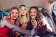 Pretty women having party in a limousine car, drinking champagne and make selfie.