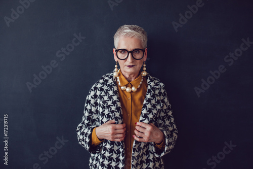 Stylish mature woman in glasses and houndstooth coat Wallpaper Mural