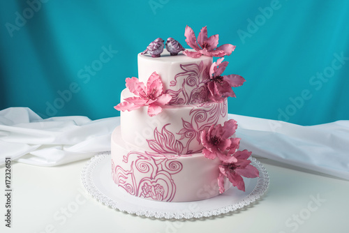 A beautiful home wedding three-tiered cake decorated with pink flowers