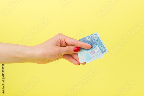Fotografía  Fifty zloty in the woman's hand, yellow background