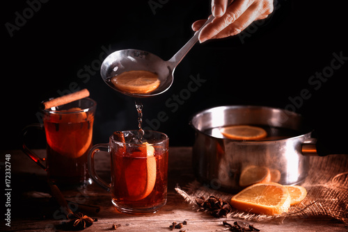 pouring hot mulled wine from in a pot and in glass mugs, Christmas spices like orange slices, cloves, star anise and cinnamon on a rustic wooden table against a dark background