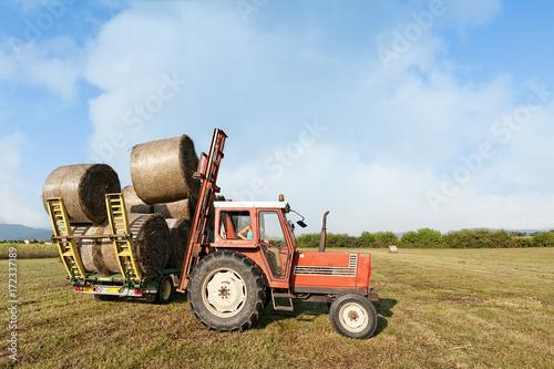 Zdjęcie XXL Scena rolnicza. Ciągnik podnoszenia beli siana na taczkę.