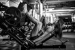 Woman doing fitness training on a leg extension push machine with weights in a gym