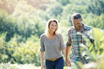Happy mature couple walking in countryside on sunny day