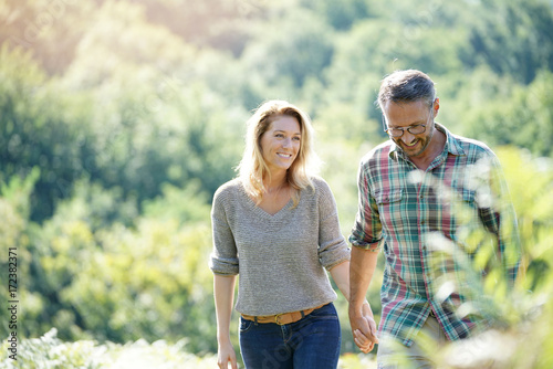 Happy mature couple walking in countryside on sunny day Fotobehang