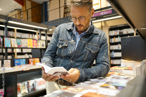 Photographie Man in bookstore looking at new books
