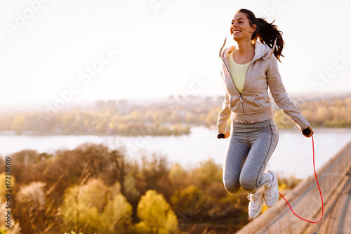 Photo  Active woman jumping with skipping rope outdoors