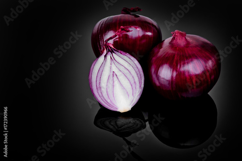 Fotografía  Red onion and half slice on black background with reflect.