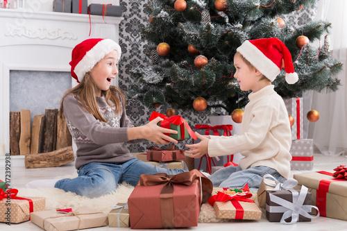 Fényképezés  Happy children in santa hats unwrapping christmas presents