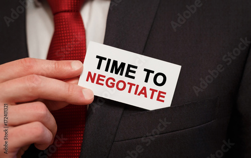 Businessman putting a card with text Time to negotiate in the pocket Canvas Print