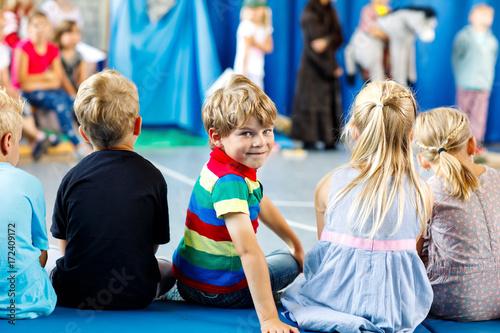 Valokuva  Children watching theater or concert at school