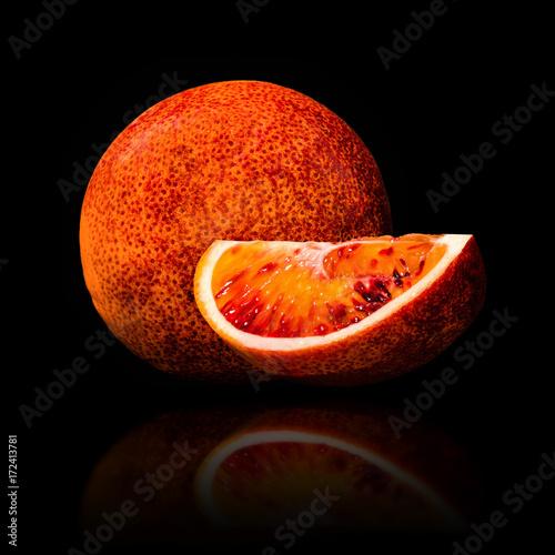 czerwona-sycylijska-pomarancza-i-jej-cwiartka-na-czarnym-tle