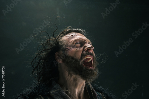 Portrait of a brutal bald-headed viking in a battle mail posing against a black background Canvas Print