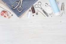 Various Fabric And Sewing Tools On The White Wooden Table