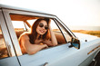 Side view of beauty woman in sunglasses sitting inside car