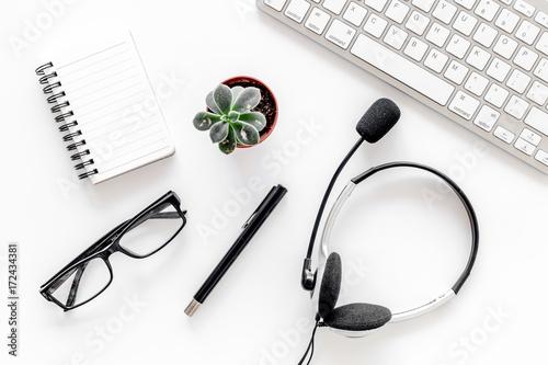 Fototapeta Worktable in call center. Headphones, keyboard and notebook on white background top view obraz na płótnie