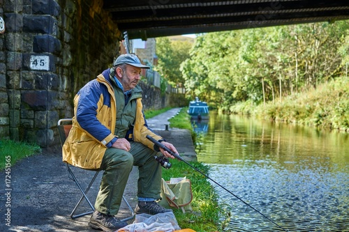 Recess Fitting Channel Man Fishing in the Huddersfield Narrow Canal, Marsden, West Yorkshire, England