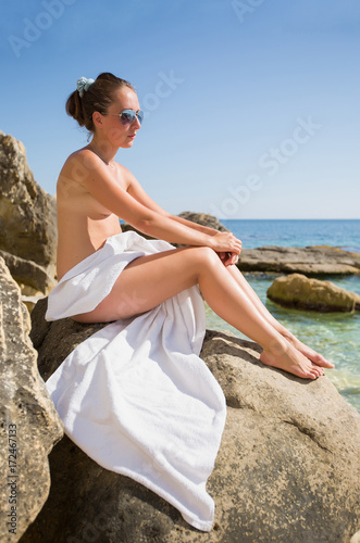 Deurstickers Ontspanning Young woman in sunglasses with white towel sits on rock