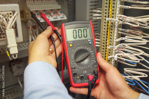 engineer tests industrial electrical circuits with multimeter in