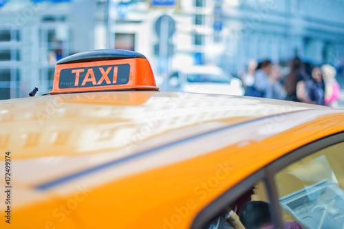 Zdjęcie XXL checker taxi na dachu żółtego samochodu w centrum dużego miasta
