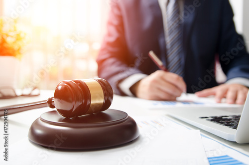 Photo Wooden gavel on table. Attorney working in courtroom.