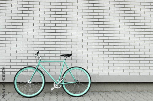 Teal bicycle next to white brick wall, copy space, no people
