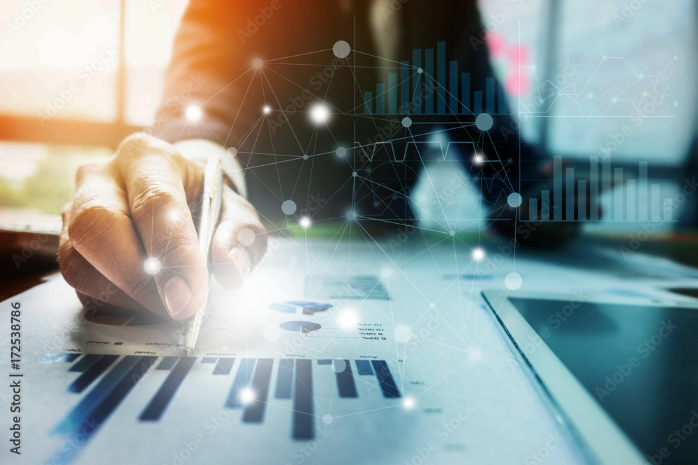 Fototapeta Close up Businessman hand holding pen and pointing at financial paperwork with social network diagram.