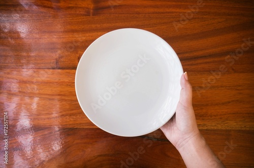 Fotografie, Obraz  Female (woman) hands hold (support) a white dish (plate) on wooden table