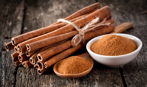 Poster Condiments Cinnamon powder on table wooden