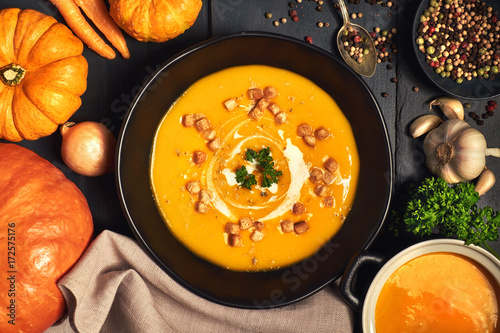 Pumpkin creme soup in a dark crockery served with croutons, crushed nuts and cream