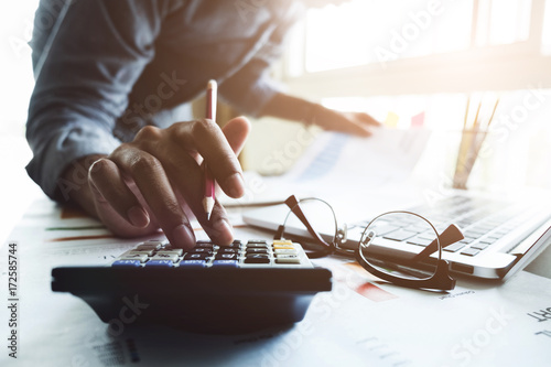 Photo Close up of businessman or accountant hand holding pen working on calculator to