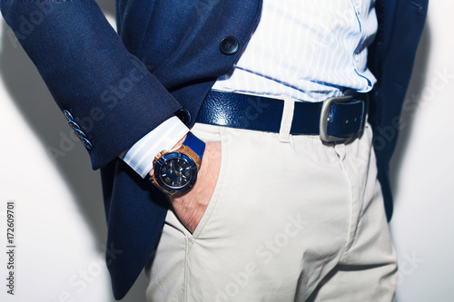 Closeup fashion image of luxury watch on wrist of man.body detail of a business man.Man's hand in a white shirt,blue jacket in a pants pocket closeup. Tonal correction.Man posing in blue suit.