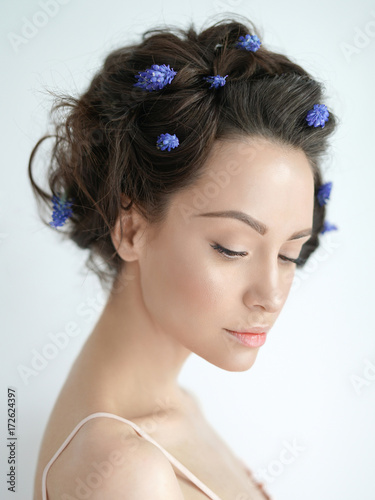 Fotografie, Obraz  Beautiful young woman with blue muscari in her hair