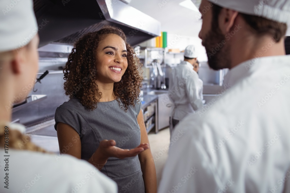 Fototapeta Restaurant manager interacting with his kitchen staff